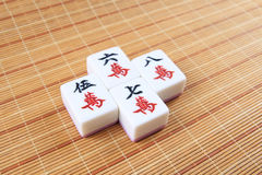 Mahjong tiles. Four mahjong tiles on the bamboo mat background, very popular game in chinese royalty free stock image