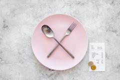 Mahlzeit ist vorbei Bill nahe Platte mit gekreuztem Löffel und Gabel auf grauem Steintischplatteansicht copyspace Lizenzfreie Stockfotos
