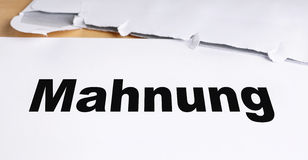 Mahnung. German dunning or reminder letter with opened envelope on desk Royalty Free Stock Photo