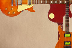 Mahogany and sunburst electric guitars and and back of guitar body on rough cardboard background, with plenty of copy space. Royalty Free Stock Photo