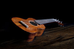 Mahogany Ukulele. A mahogany ukulele laying on old wood floor.The ukulele is a member of the lute family of instruments; it generally employs four nylon or gut Stock Photo