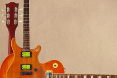 Mahonie en zonnestraal elektrische gitaren en hals op ruwe kartonachtergrond, met overvloed van exemplaarruimte stock afbeelding