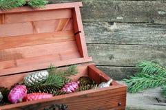 Mahoniowy drewniany pudełko z choinek dekoracjami, złoto konusuje i sosna rozgałęzia się na drewnianym szarym tle Zima wakacji co zdjęcia stock