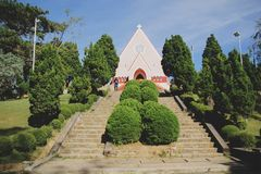 Mai Anh Cathedral, Da lat, Viet name - November 26,2016: Beautiful church with a lots of trees on the blue sky stock photography