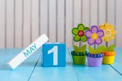 1. Mai Bild von kann 1 hölzerner Farbkalender auf weißem Hintergrund mit Blumen Frühlingstag, leerer Raum für Text 1. Lizenzfreies Stockfoto