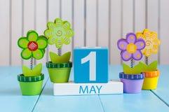 1. Mai Bild von kann 1 hölzerner Farbkalender auf weißem Hintergrund mit Blumen Frühlingstag, leerer Raum für Text Lizenzfreies Stockfoto