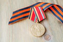 9 mai fond Médaille de jubilé de grande guerre patriotique et de ruban de St George sur le fond en bois photos libres de droits