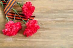 9 mai fond - oeillets rouges et ruban de George se trouvant sur le fond en bois Photographie stock libre de droits