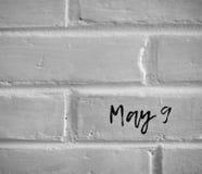 ` Am 9. Mai ` GESCHRIEBEN AUF WEISSE EINFACHE BACKSTEINMAUER Lizenzfreies Stockfoto