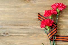 9. Mai Hintergrund - rote Gartennelken und George-Band, das auf dem hölzernen Hintergrund liegt Lizenzfreie Stockbilder