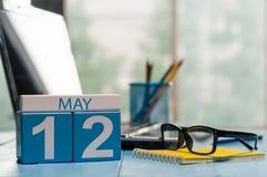 12 mai Jour 12 de mois, calendrier sur le fond de local commercial, lieu de travail avec l'ordinateur portable et verres Printemp Photos stock
