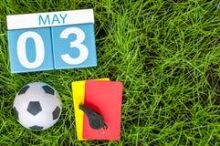 3 mai Jour 3 du mois, calendrier sur le fond d'herbe verte du football avec des accessoires du football Printemps, l'espace vide Images libres de droits