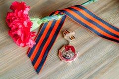 9. Mai Karte - Nahaufnahme der Medaille des großen patriotischen Krieges mit roter Gartennelke und George-Band Lizenzfreies Stockfoto
