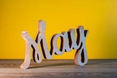 Mai - nom découpé en bois de mois de ressort Calendrier sur la table de local commercial, lieu de travail au fond jaune Le printe Image libre de droits