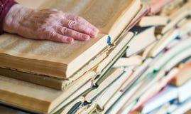 Mai non troppo vecchio imparare - le mani del libro di lettura della donna anziana fotografia stock