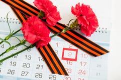 9. Mai - rote Gartennelke mit George-Band, das auf dem Kalender mit am 9. Mai Datum liegt Lizenzfreies Stockbild