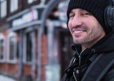 MAI sorridente nel headphoneswalk nelle vie di inverno immagini stock