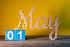 1. Mai Tag 1 des Monats, hölzerner geschnitzter Kalender auf gelbem Hintergrund Frühlingszeitkonzept Lizenzfreie Stockbilder