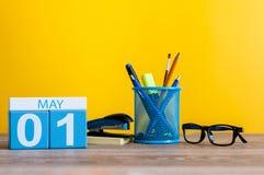 1. Mai Tag 1 des Monats, Kalender auf Geschäftsbürotisch, Arbeitsplatz am gelben Hintergrund Frühlingszeit… Rosenblätter, natürli Stockbild