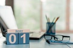 1. Mai Tag 1 des Monats, Kalender auf Geschäftslokalhintergrund, Arbeitsplatz mit Laptop und Gläser Frühlingszeit, leer Lizenzfreie Stockbilder