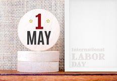 1. Mai Tag (internationaler Werktag) auf Rundholz- und Fotorahmen, Feiertagskonzept Lizenzfreies Stockfoto