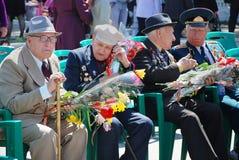 9. Mai. Victory Day. Ältere Männer, Veterane des Krieges, sitzend mit Medaillen und Blumen Stockfotos