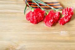 9. Mai Victory Day-Hintergrund Drei rote Gartennelken und St- Georgeband, das auf dem hölzernen Hintergrund liegt Stockbilder