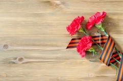 9. Mai Victory Day-Hintergrund Rote Gartennelken und St- Georgeband, das auf dem hölzernen Hintergrund liegt Lizenzfreie Stockbilder