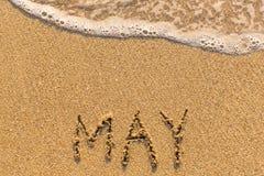 Mai - Wort gezeichnet auf den Sandstrand mit der weichen Welle Lizenzfreie Stockfotografie