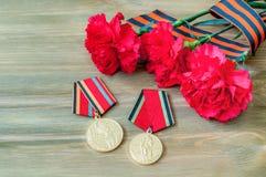 9. Mai Zusammensetzung - Medaillen des großen patriotischen Krieges mit roten Gartennelken und George-Band Lizenzfreie Stockbilder