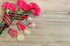 9. Mai Zusammensetzung - Medaillen des großen patriotischen Krieges mit roten Gartennelken und George-Band Lizenzfreies Stockfoto