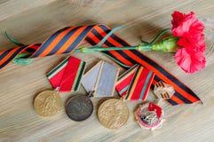 9. Mai Zusammensetzung - Medaillen des großen patriotischen Krieges mit roten Gartennelken und George-Band Stockbild