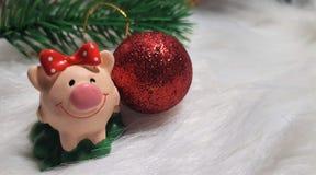 Maiale del giocattolo e decorazione di inverno, congratulazioni sulla festa Simbolo dell'anno del maiale sui precedenti delle luc fotografia stock