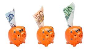 Maiali arancioni con soldi Fotografia Stock