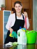 Maid in apron dusting and wiping Stock Photos