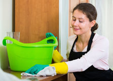 Maid in apron dusting and wiping Royalty Free Stock Photography