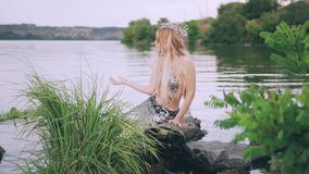Maid with blond long straight hair, a mermaid pearl crown on her head and a luxurious silver tail, sitting on a log near. The lake, straightens her hair stock video