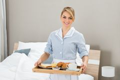 Maid With Breakfast Tray. Happy Maid Carrying Breakfast Tray In Hotel Room Stock Photos