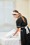 Maid bringing fresh bathrobe in hotel room Royalty Free Stock Image