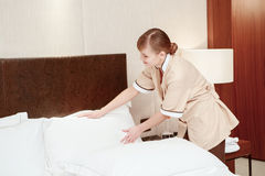 Maid changes bedclothes in hotel Stock Photo