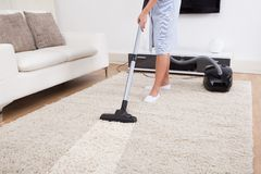 Maid cleaning carpet with vacuum cleaner royalty free stock photography