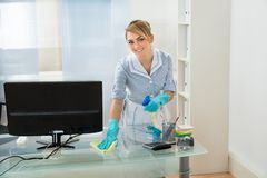 Maid cleaning desk in office royalty free stock photography