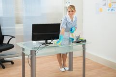 Maid cleaning desk in office Royalty Free Stock Image