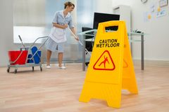Maid cleaning floor in office Royalty Free Stock Images