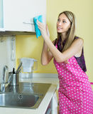 Maid cleaning furniture in kitchen Stock Photos