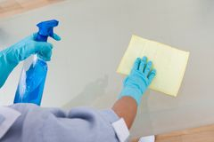 Maid cleaning glass table Royalty Free Stock Photo