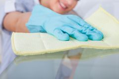 Maid cleaning glass table royalty free stock photography