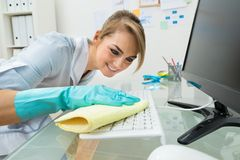 Maid cleaning keyboard at desk Royalty Free Stock Photos