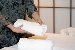 Maid cleaning at the spa. The girl folds a towel, prepares a workplace in the spa for the reception of clients. The maid is preparing a room for the spa salon Royalty Free Stock Photo