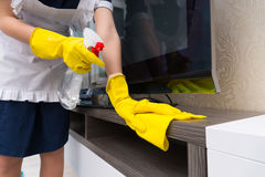 Maid cleaning a television cabinet Royalty Free Stock Photo